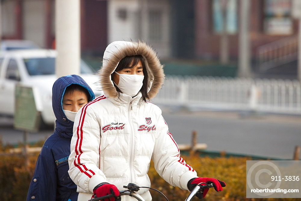 Cyclists in Beijing wearing smog masks to help protect against the awful air pollution, Beijing, China, Asia