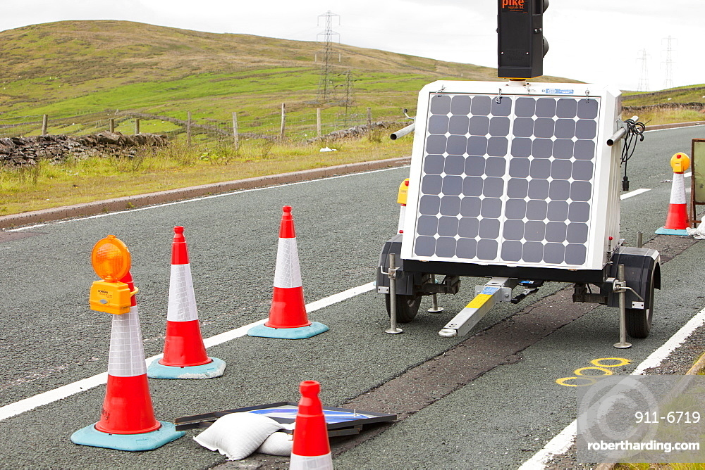 A set of traffic lights at road works, powered by a solar panel on Shap summit in the Lake District, Cumbria, England, United Kingdom, Europe