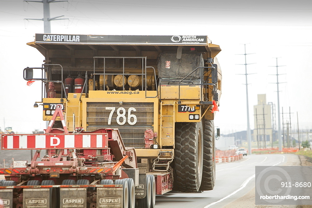 Truck hauls an oversize load, a massive dump truck used in the tar sands mines, on the road towards Fort McMurray, the centre of the tar sands industry, Alberta, Canada, North America