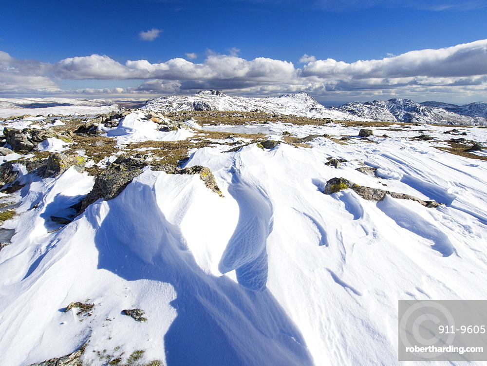 Drifting snowpack on Scafell Pike, looking towards Bow Fell and Crinkle Crags, Lake District, Cumbria, England, United Kingdom, Europe