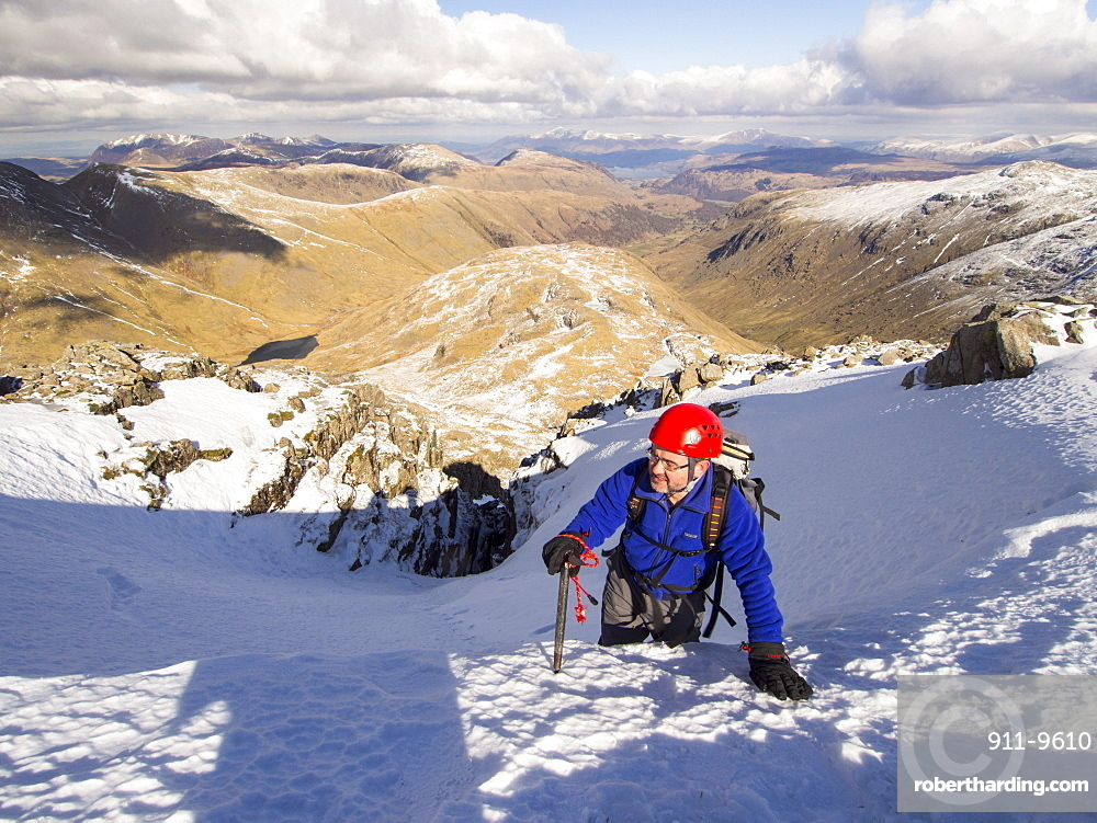 A climber topping out in Custs Gully on Great End, a grade one winter route, with Great Gable in the background, Lake District, Cumbria, England, United Kingdom, Europe