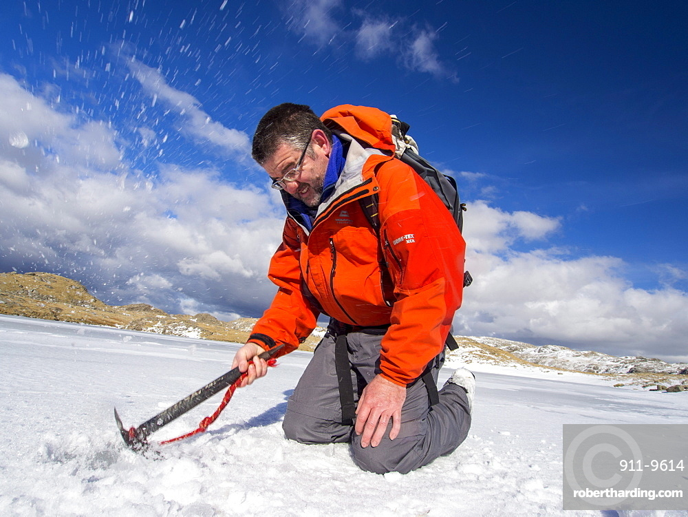A mountaineer testing the thickness of ice on Sprinkling Tarn to see if it is safe to walk on, Lake District, Cumbria, England, United Kingdom, Europe