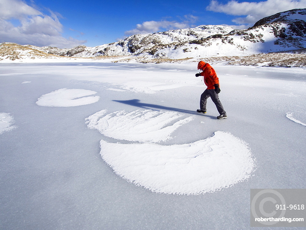 A climber on Sprinkling Tarn at the head of Borrowdale, looking towards Glaramara, with drifted snow making patterns on the ice, Lake District, Cumbria, England, United Kingdom, Europe