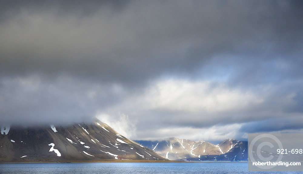 Landscape scenic view with snow caped mountains, ocean, and clouds, Penkigney Fjord (Bering Sea ) Russia, Asia