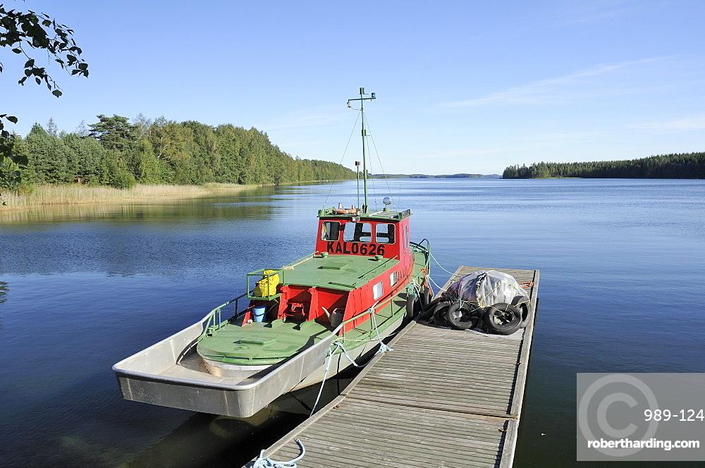 Boat moored at a jetty on Lake Puruvesi, a branch of Lake Saimaa near Kerimaki, Finland, Scandinavia, Europe