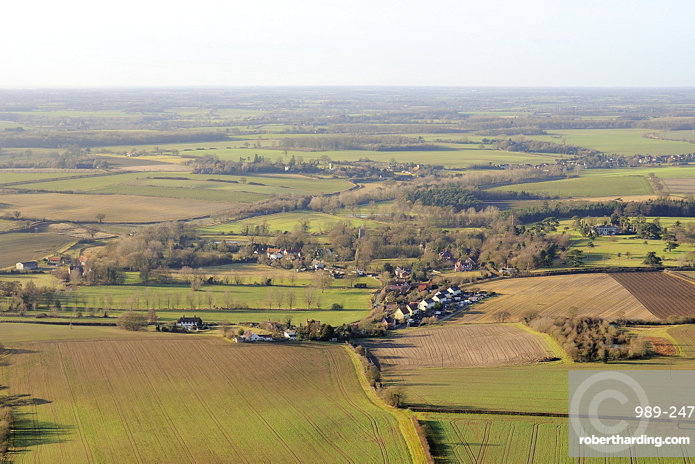 Aerial view of rolling rural landscape with small villages, winter wheat fields and pastureland, Suffolk, England, United Kingdom, Europe