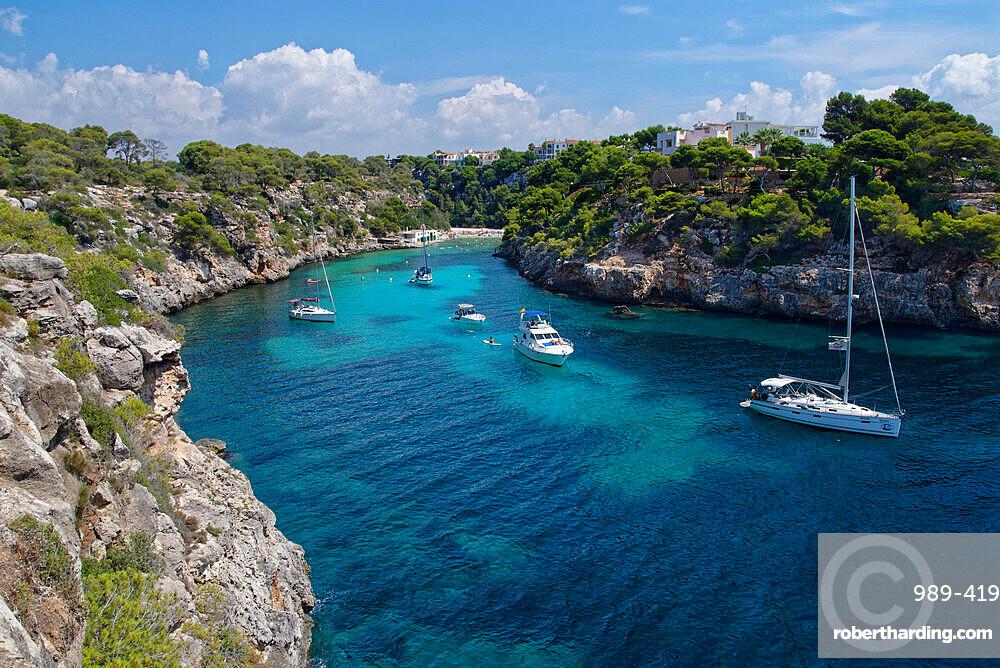 Yachts moored in the cove at Cala Pi, viewed from narrow cliff top coast path, Mallorca south coast.