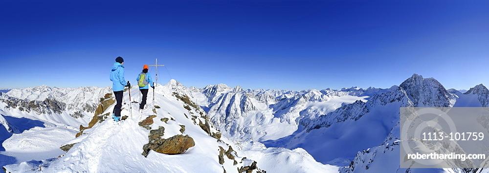 Two female back-country skiers beside Kuhscheibe summit cross, Stubai Alps, Tyrol, Austria