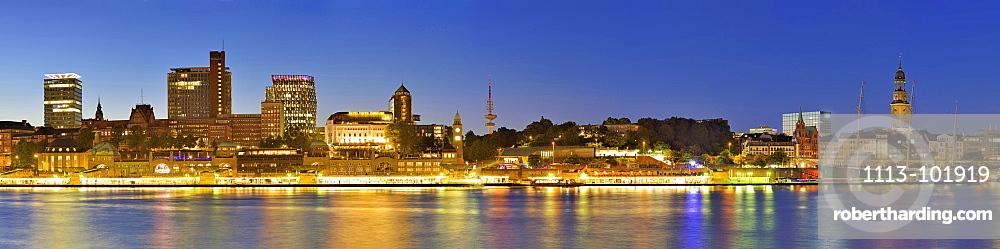 Panorama of Hamburg with view over the river Elbe to illuminated St. Pauli-Landungsbruecken with skyscrapers, Pegelturm, Heinric
