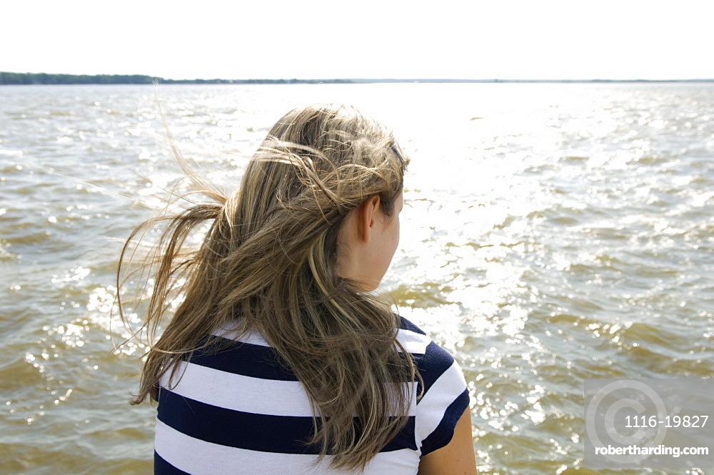 Teenager sitting by a lake, Victoria Beach, North of Winnipeg, Manitoba, Canada