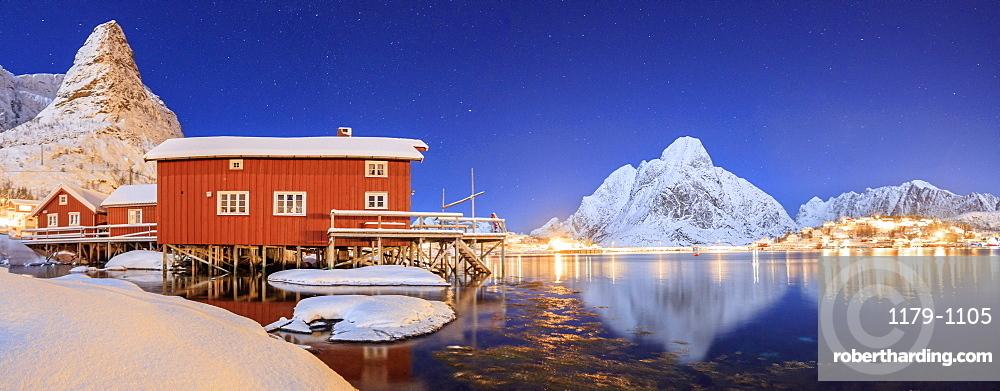 Panoramic view of snowy peaks and the frozen sea on a starry winter night, Reinevagen Bay, Nordland, Lofoten Islands, Arctic, Norway, Scandinavia, Europe