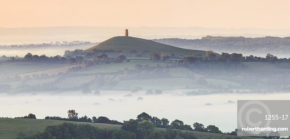 Glastonbury Tor, Somerset, rising above a misty landscape on an autumn morning.