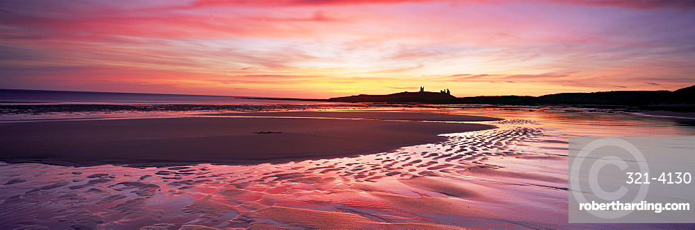 Embleton Bay at sunrise, low tide, with Dunstanburgh Castle in distance, Northumberland, England, United Kingdom, Europe