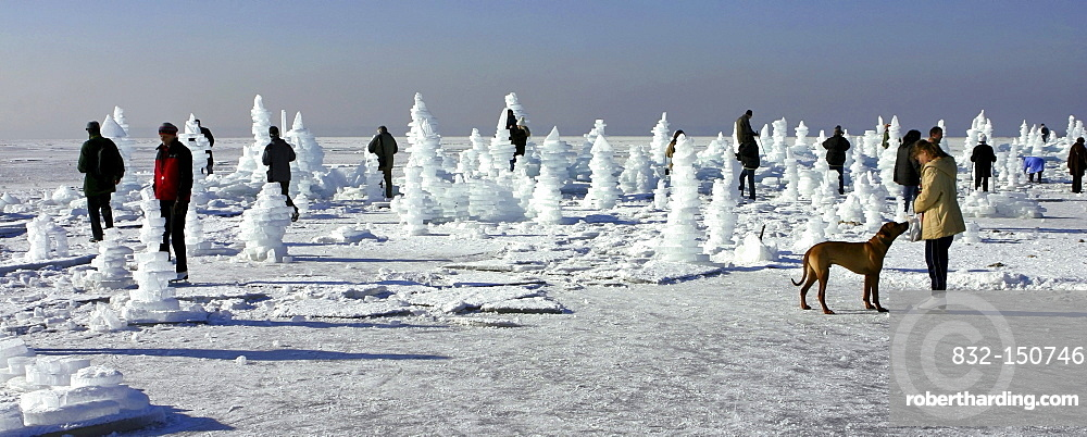 People standing amogst man-made ice towers on frozen lake Chiemsee, Chiemgau, Upper Bavaria, Germany, Europe