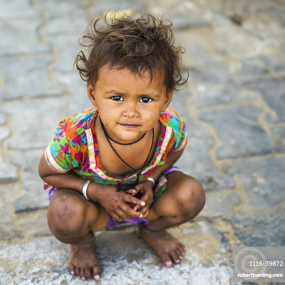 Portrait of a young girl crouching on the street, Jaipur, Rajasthan, India