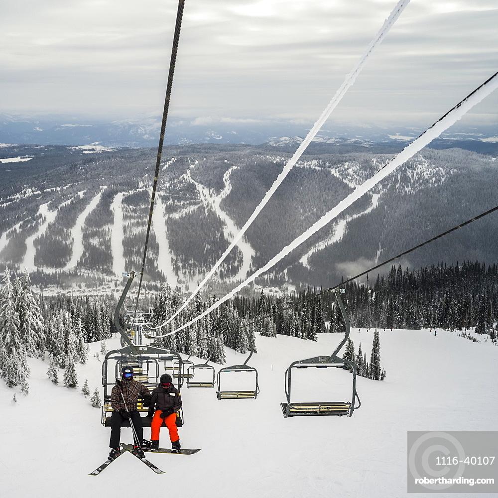 Skiers on a chairlift at Sun Peaks ski resort, Kamloops, British Columbia, Canada