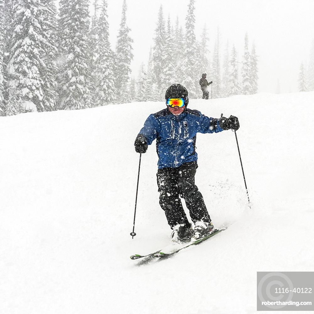 Skier going downhill in a heavy snowfall at Sun Peaks Resort, Kamloops, British Columbia, Canada