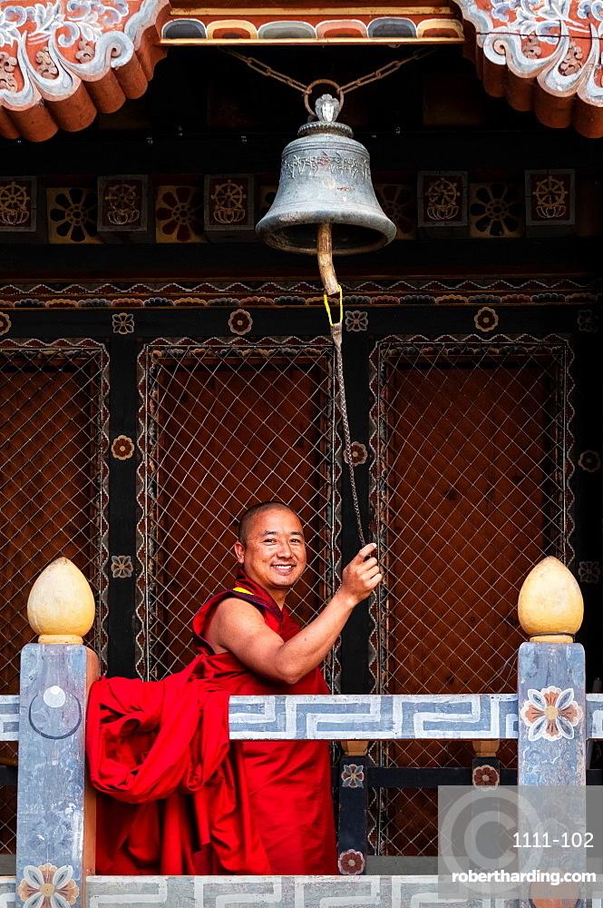 Buddhist monk ringing prayer bell, Trongsa Dzong, Trongsa, Bhutan, Asia