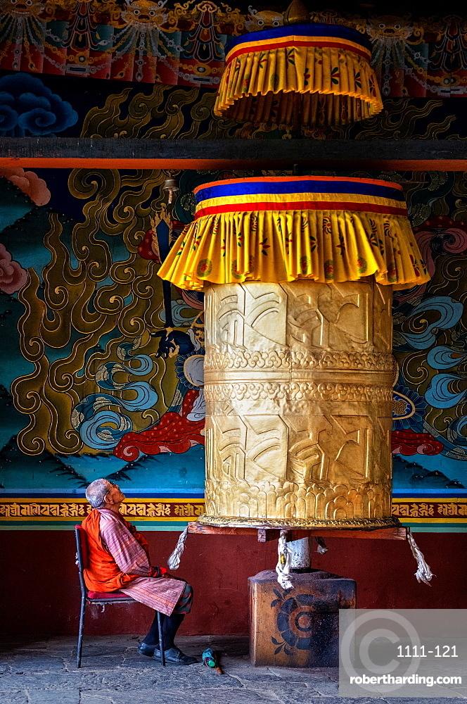 Portrait of elderly Buddhist monk turning prayer wheel, Punakha Dzong, Bhutan, Asia
