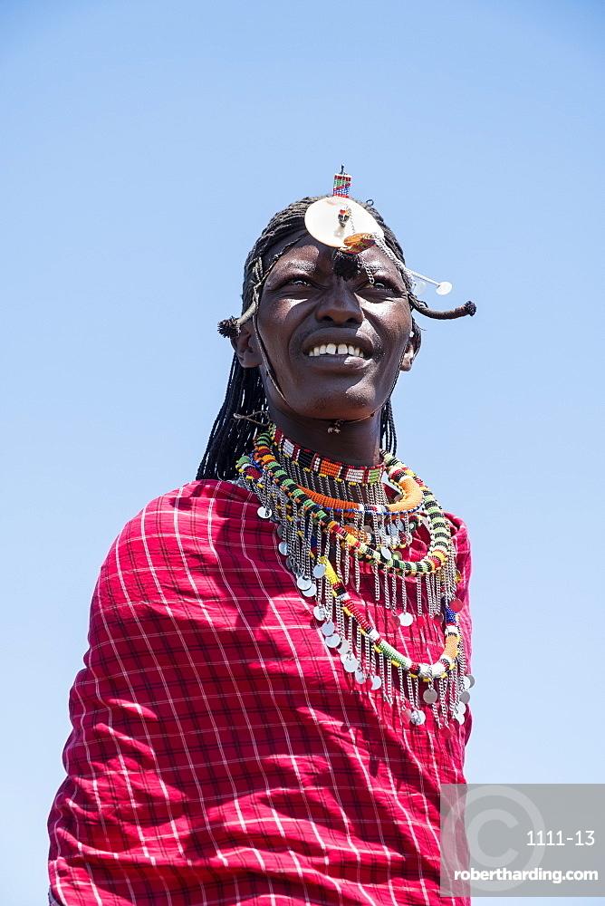 Portrait of a single Masai Mara man wearing traditional jewelry, headpiece and clothes, Masai Mara National Reserve, Kenya, East Africa, Africa