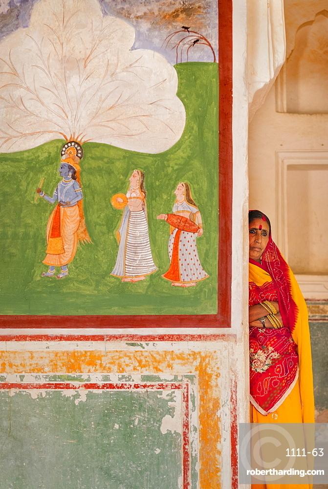 Hindu woman by artwork at Amber Fort in Jaipur, Rajasthan, India, Asia