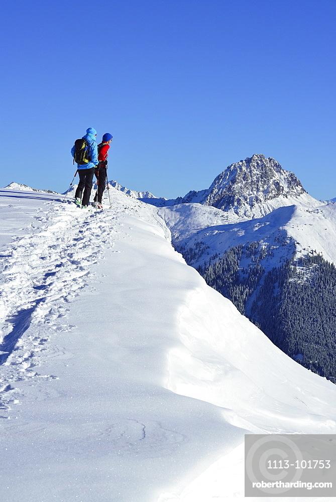 Two female back-country skiers ascending to mount Steinberg, Kitzbuehel Alps, Tyrol, Austria