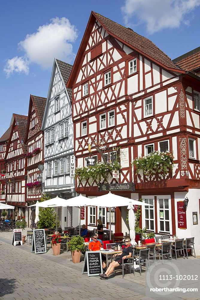 People sitting outside Gasthaus Zum Schmied restaurant near half-timbered houses in the old town, Ochsenfurt, Franconia, Bavaria