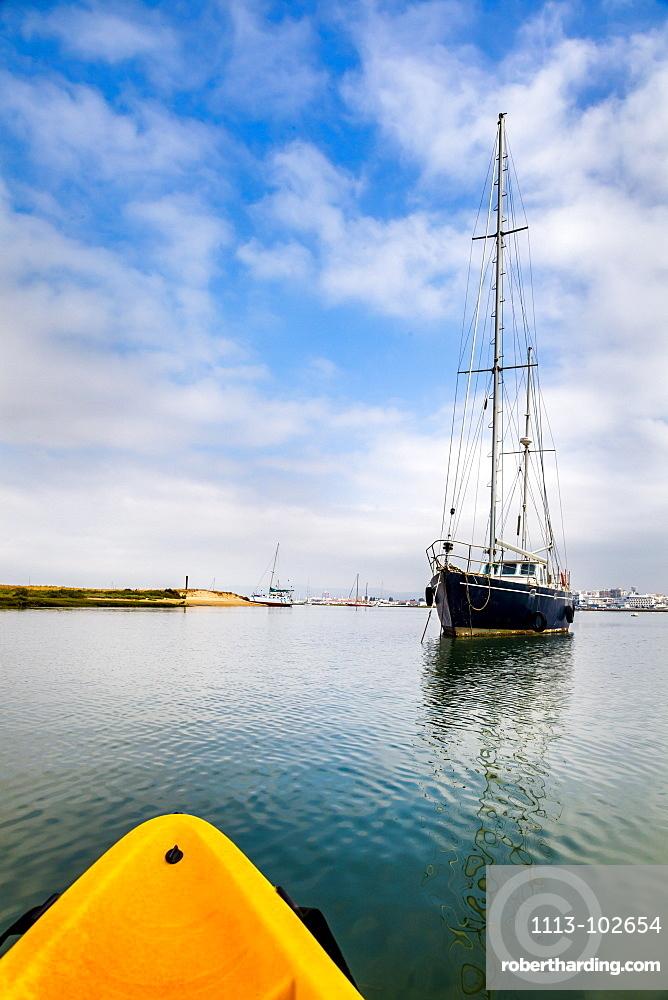 Kayak tour and sailing boat in the lagoon, Parque Natural da Ria Formosa, Faro, Algarve, Portugal