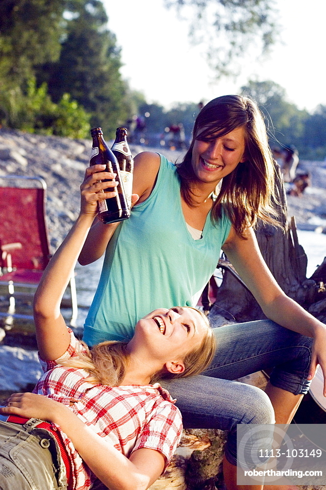 Two young women drinking beer, Munich, Bavaria, Germany