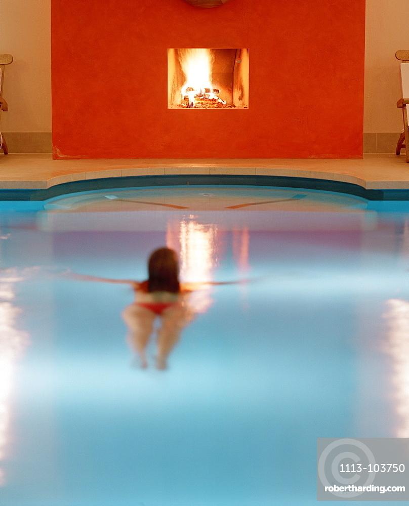 Woman swimming in a pool, chimney in background, Hotel Neuklostersee, Nakenstorf, Mecklenburg-Western Pomerania, Germeny, MR, PR