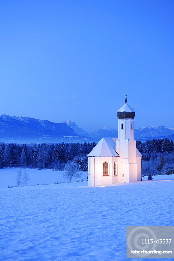 Snow covered church in front of Zugspitze and Ammergau range in the evening, Penzberg, Werdenfelser Land, Upper Bavaria, Bavaria, Germany, Europe