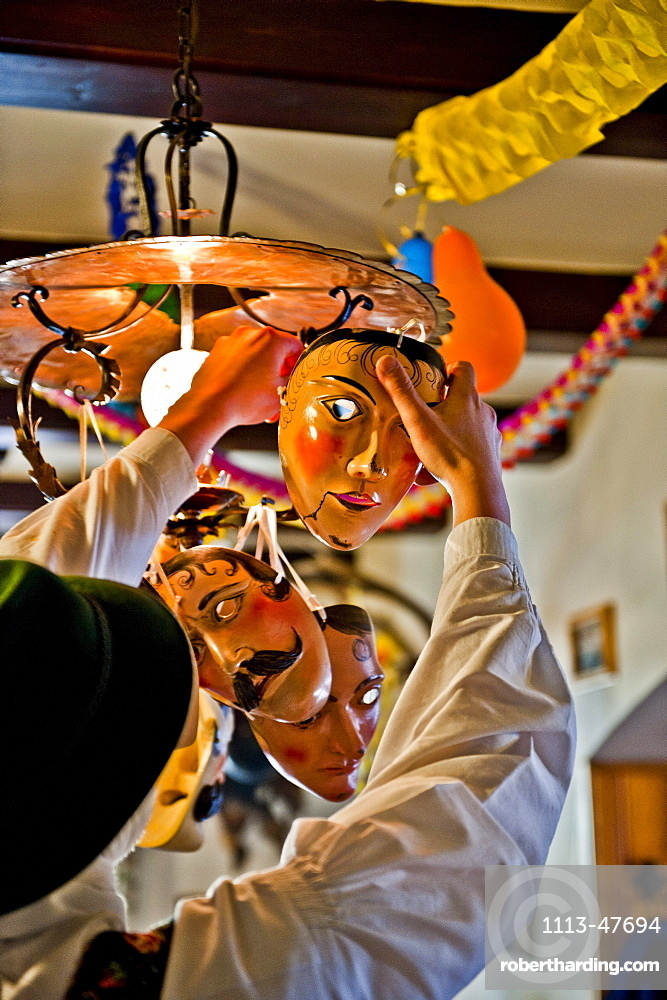Disguised person hanging masks on a lamp, Mittenwald, Bavaria, Germany, Europe