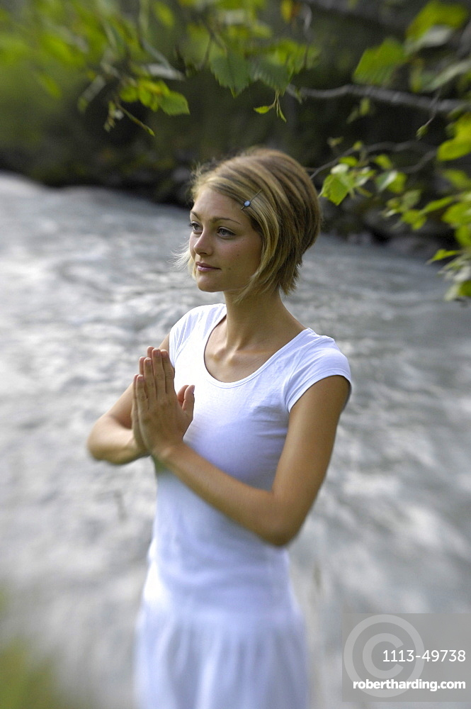 Young woman doing yoga at the banks of a river, Alto Adige, South Tyrol, Italy, Europe