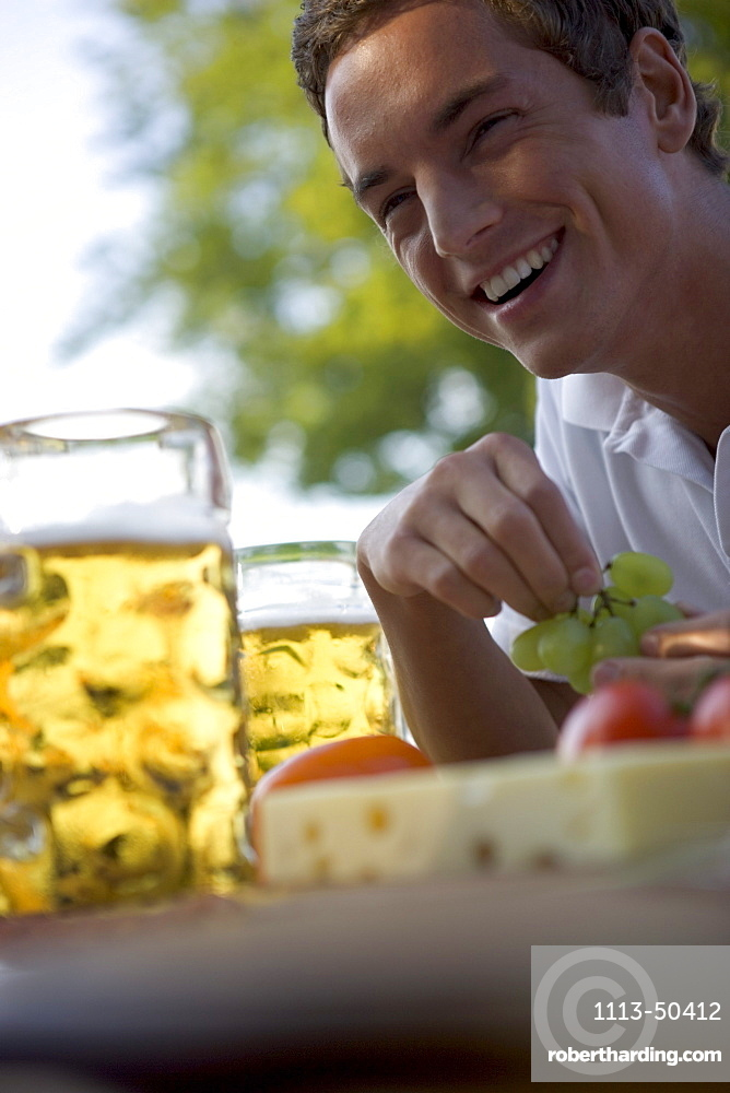 Young man with snack and beer stein in beergarden near Lake Starnberg, Bavaria, Germany