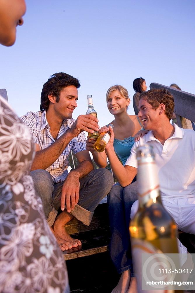 Friends partying on jetty, Lake Starnberg, Bavaria, Germany