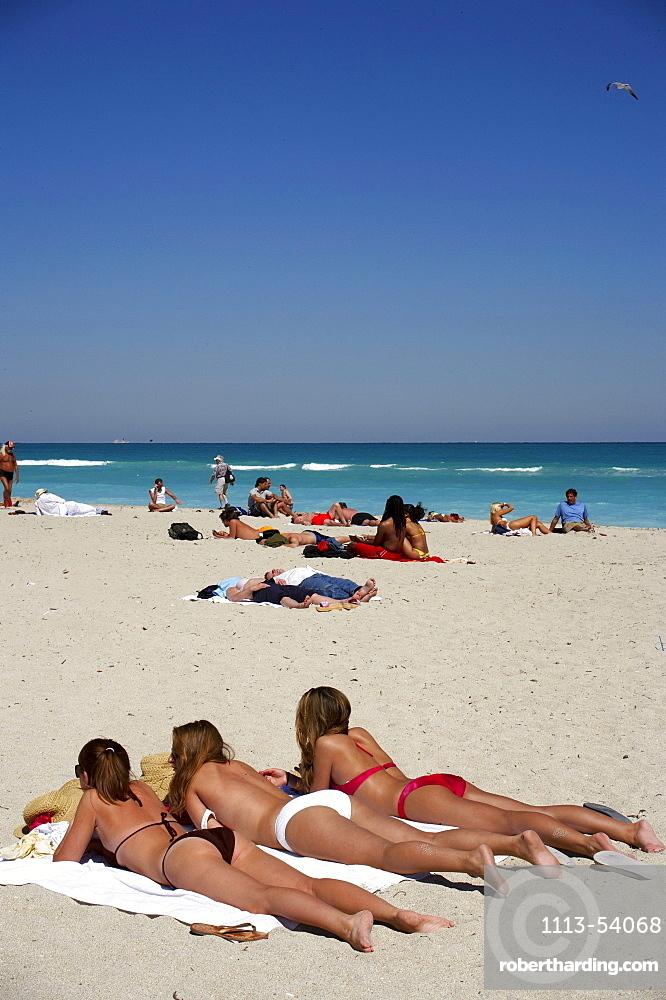 Three young women lying in the sun, beach life, Art Deco Historic Destric, South Beach, Miami, Florida, USA