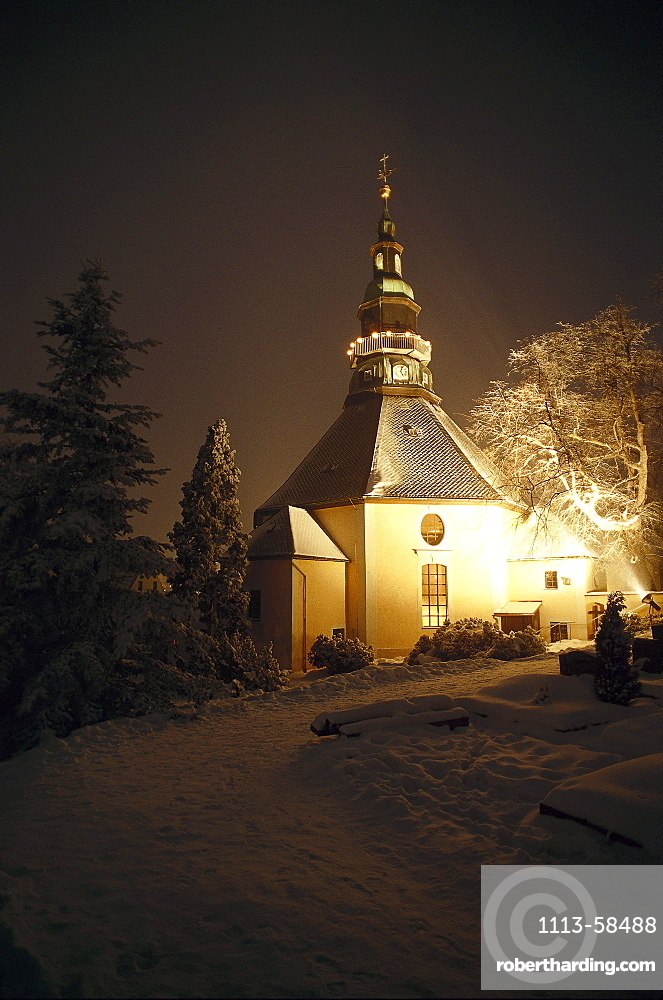 Illuminated chapel in the Erz Mountains at night in winter, Saxony, Germany