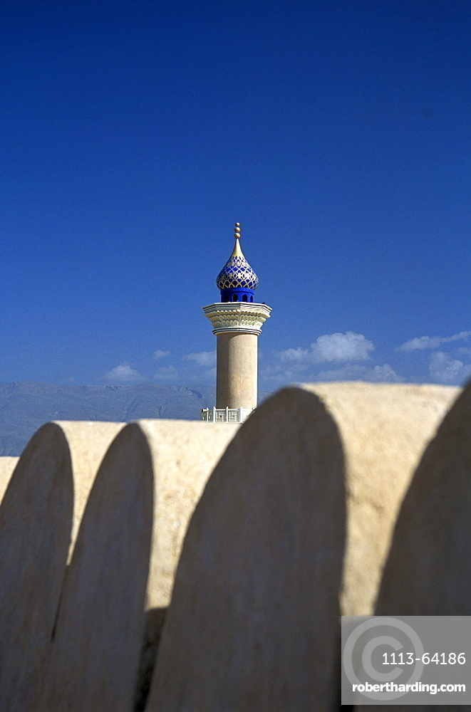 Fort and minaret under blue sky, Nizwa, Oman, Middle East, Asia