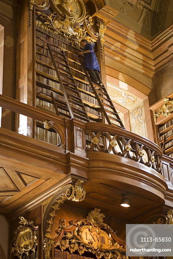 Man sorting books, standing on a ladder, Prunksaal of Nationalbibliothek National Libary, Vienna, Austria