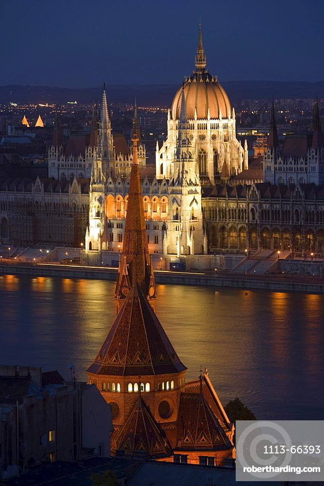View over Calvinist Church and Danube river to the illuminated Parliament at night, Pest, Budapest, Hungary