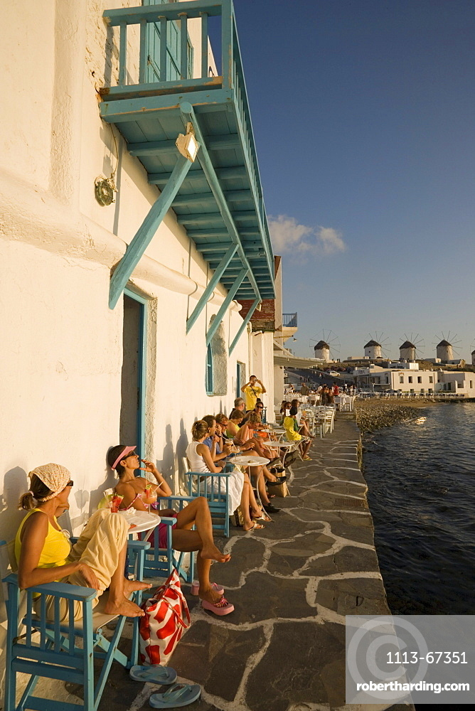 People sitting in Caprice Bar directly at sea, windmills in background, Little Venice, Mykonos-Town, Mykonos, Greece