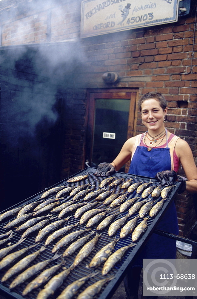 Woman presenting smoked kippers, Orford, Suffolk, England00058424