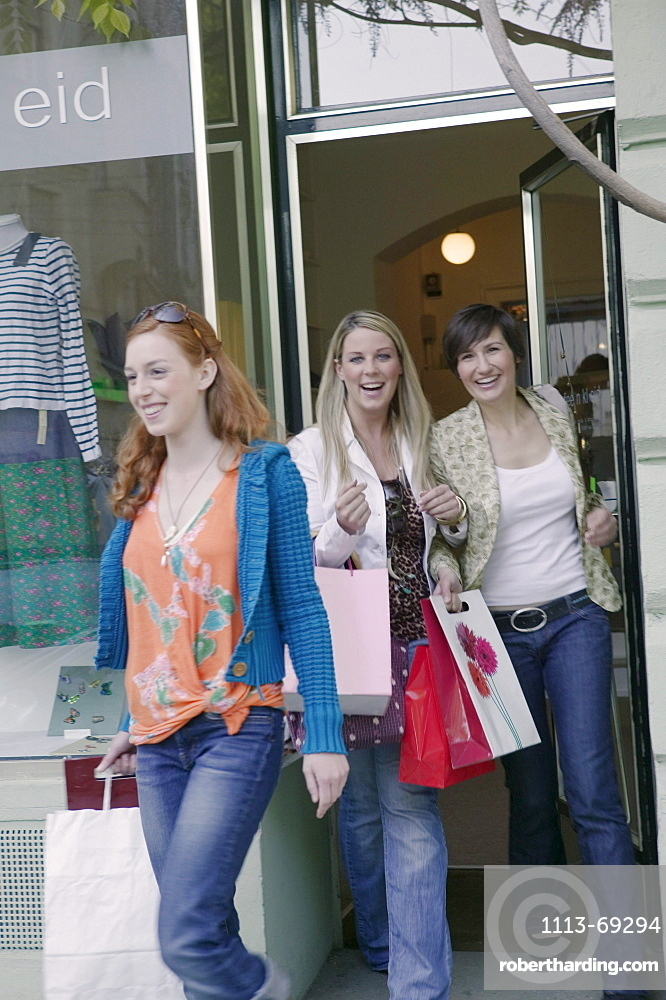 Young women walking out of shop with shopping bags