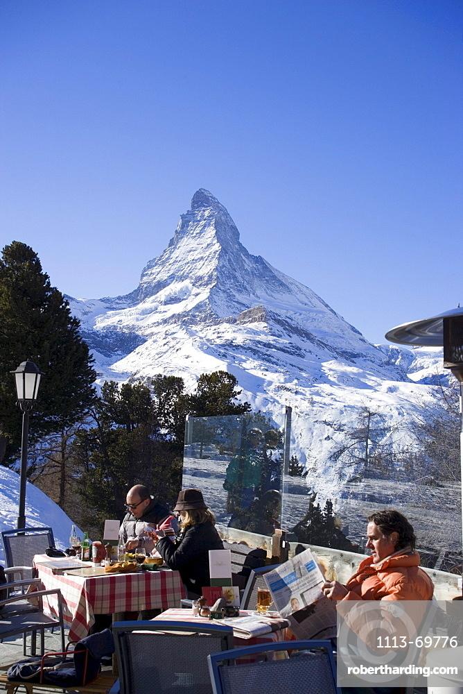 People relaxing on terrace of Hotel and Restaurnat Riffelberg (2582 m), Matterhorn (4478 m) in background, Zermatt, Valais, Switzerland