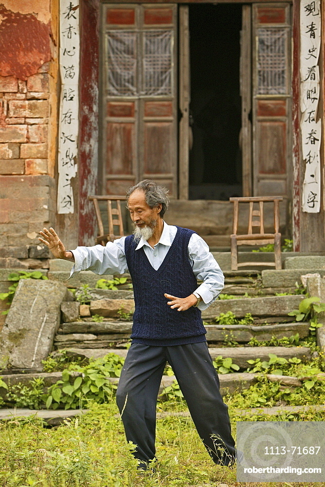 Taichi master demonstrating Taichi in front of his old house at the foot of Mount Wudang, Wudang Shan, Taoist mountain, Hubei province, Wudangshan, Mount Wudang, UNESCO world cultural heritage site, birthplace of Tai chi, China