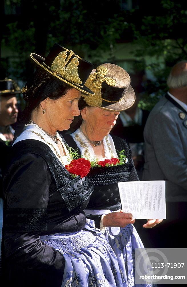 Two elderly women wearing dirndl dresses, reading the songs for the religious service, pilgrimage to Raiten, Schleching, Chiemgau, Upper Bavaria, Bavaria, Germany