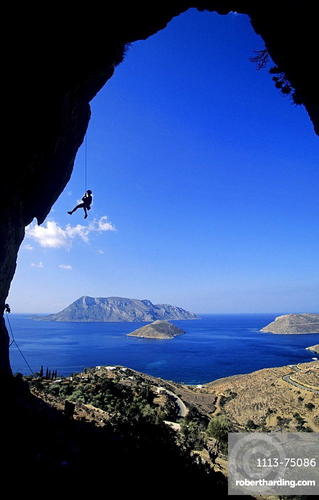 Kalymnos, Greece, Aegean Sea, a climber abseils in a cave above the sea. Kalymnos, Greece, Aegean Sea, Europe