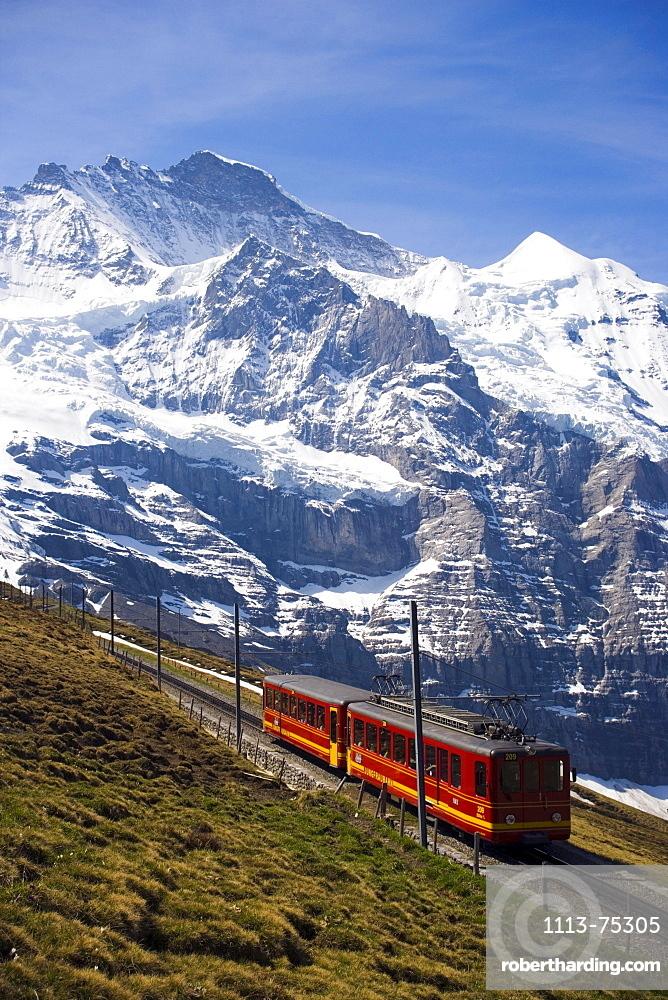 Jungfraubahn leaving station Kleine Scheidegg (2061 m), on the way to Jungfraujoch (highest railway station in Europe), Jungfrau in the background, Bernese Oberland (highlands), Canton of Bern, Switzerland