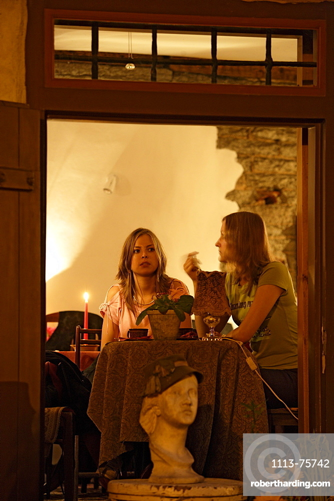 Two young women in Cafe Chocolaterie in the evening, Vene street, Tallinn, Estonia