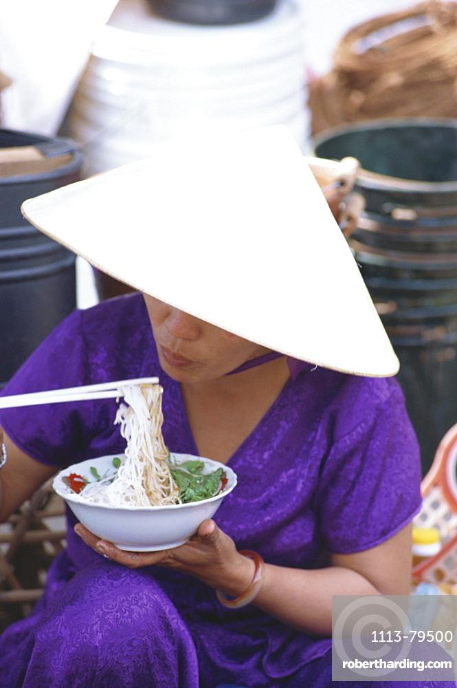 Woman eating noodles at a market, City Scape, Hoi An, Vietnam